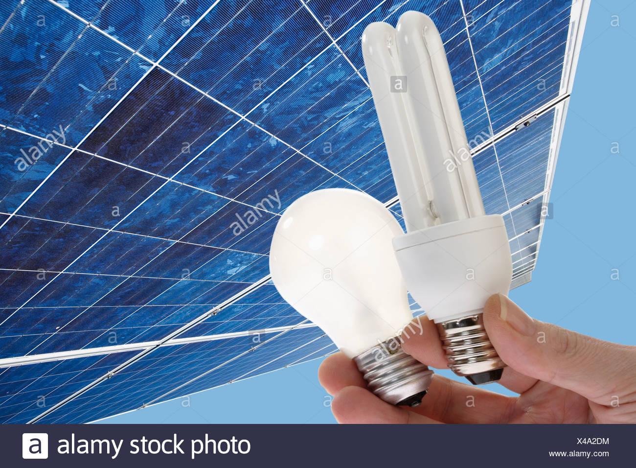 La mano que sujeta el ahorro de energía, la bombilla de luz contra un panel solar, de cerca. Imagen De Stock