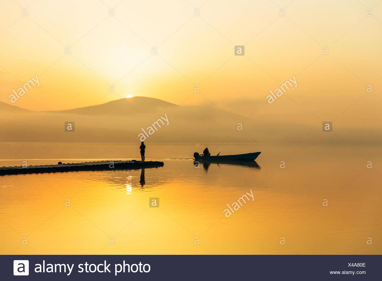 Japón, la Península de Izu, siluetas de dos personas en el barco y el muelle Imagen De Stock