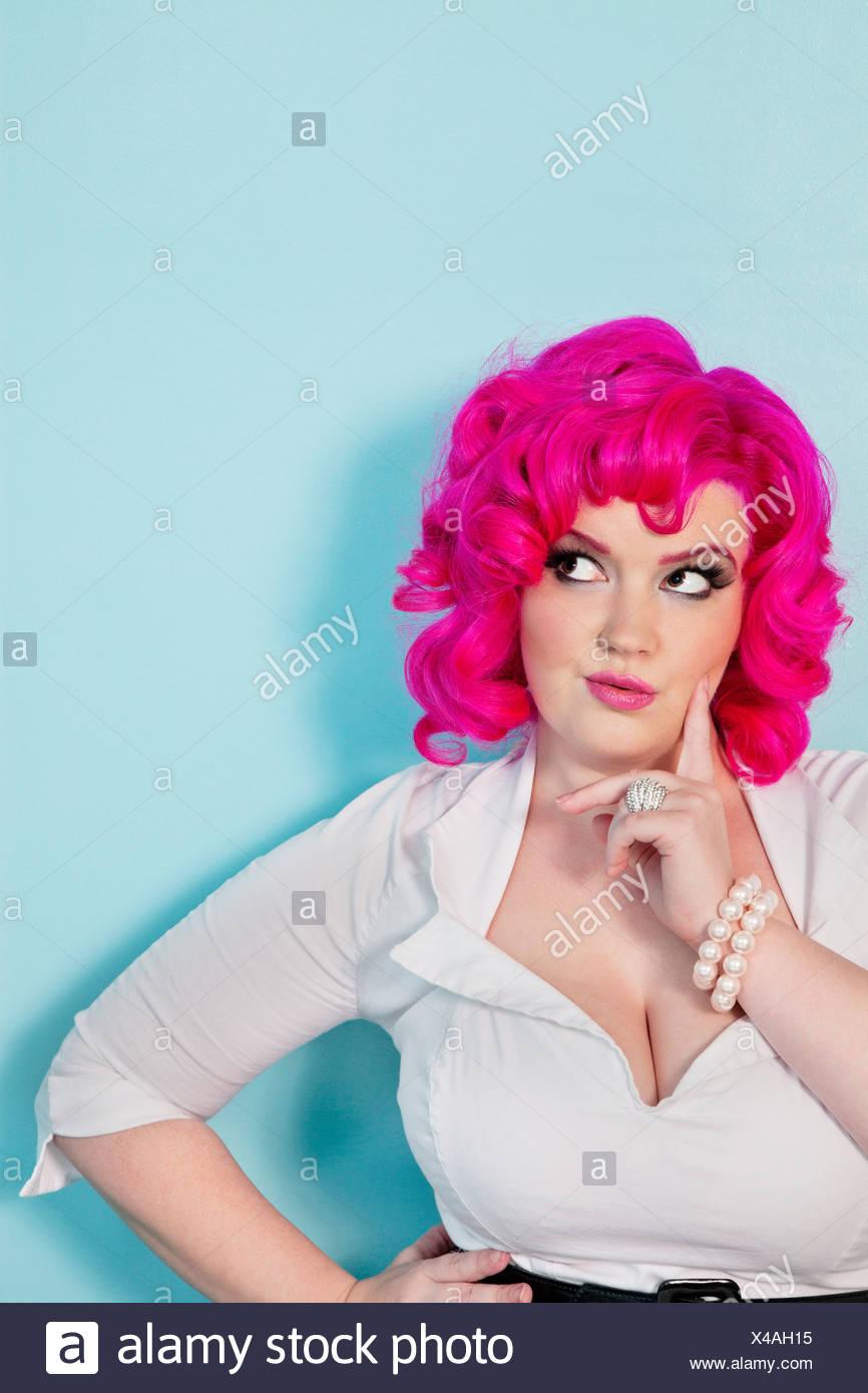 Mujer joven soñando despierto con el dedo en la cara sobre fondo de color Foto de stock