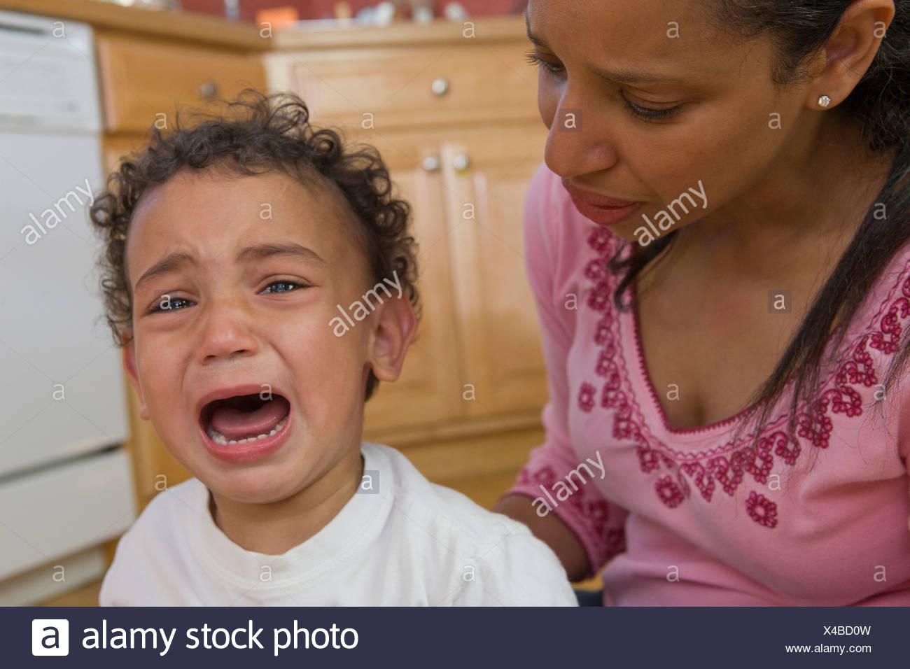 Preocupado Hispanic madre llorando al lado de su hijo Foto de stock