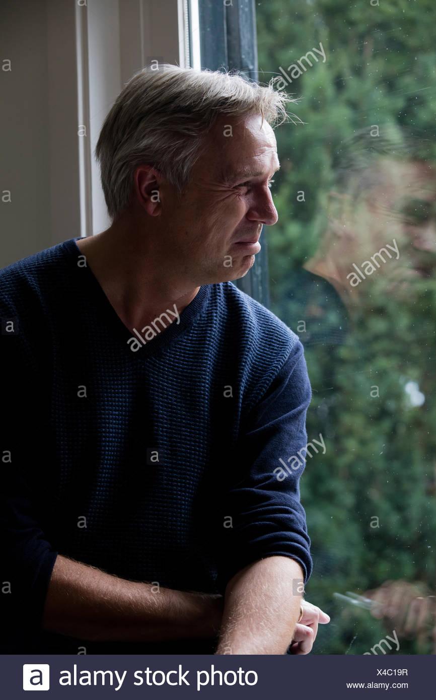 Mueca en la cara: el hombre está sonriendo y parece infeliz, podría ser burnout Imagen De Stock