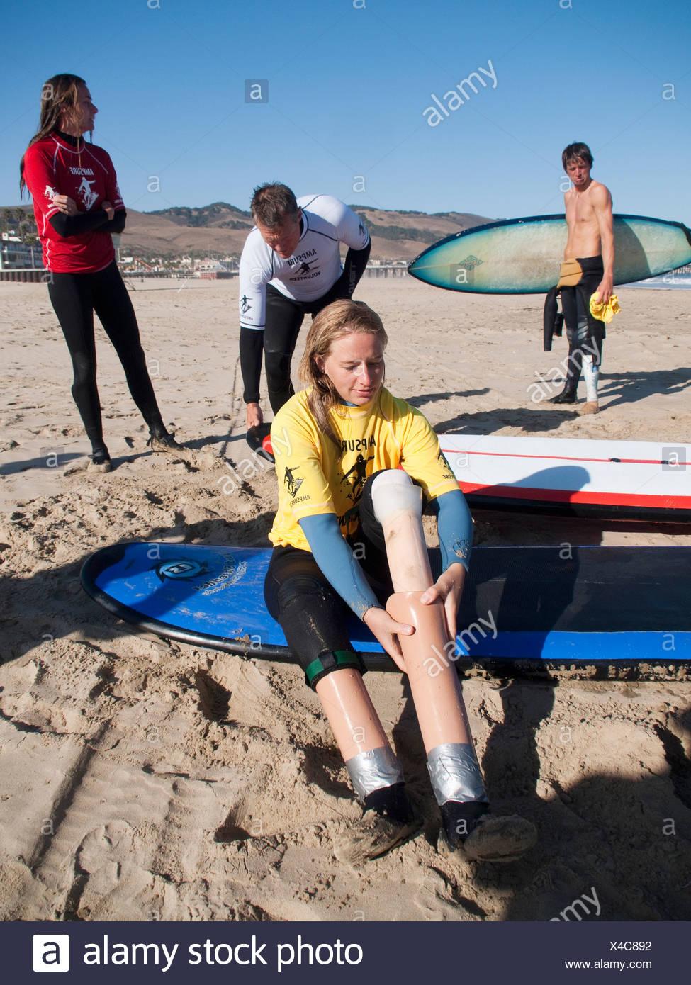 """Monica DeNatley, quien nació sin piernas, se vacía el agua y la arena de sus """"patas"""" de surf durante las Clínicas de Surf patrocinado Foto de stock"""
