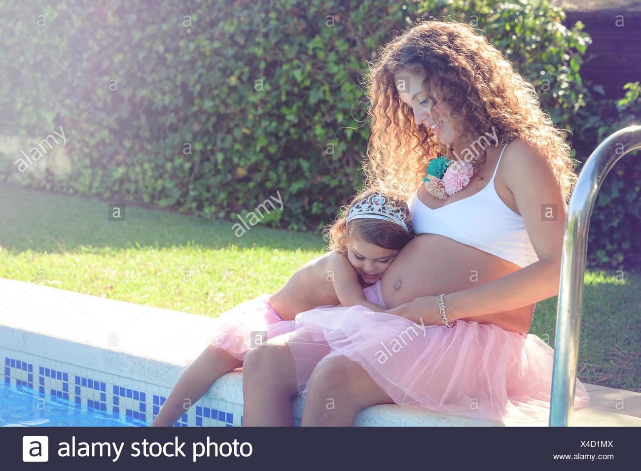 Mujer embarazada sentada con mi hija por piscina Foto de stock