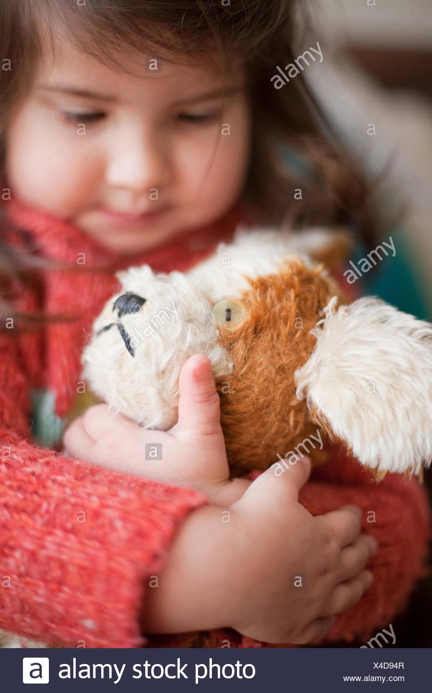 Niña abrazando perro de juguete Imagen De Stock