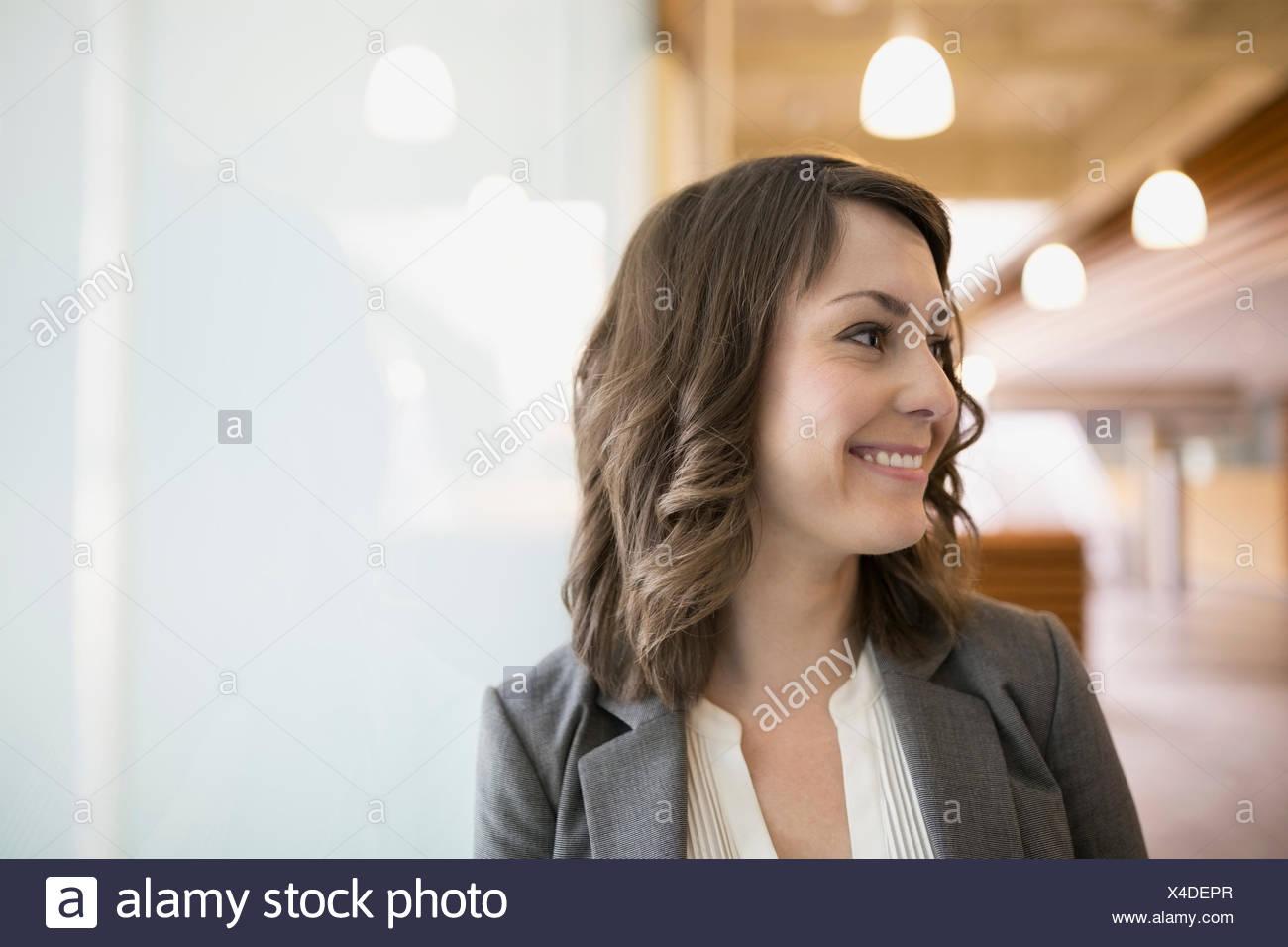 Retrato sonriente morena empresaria mirando lejos Imagen De Stock