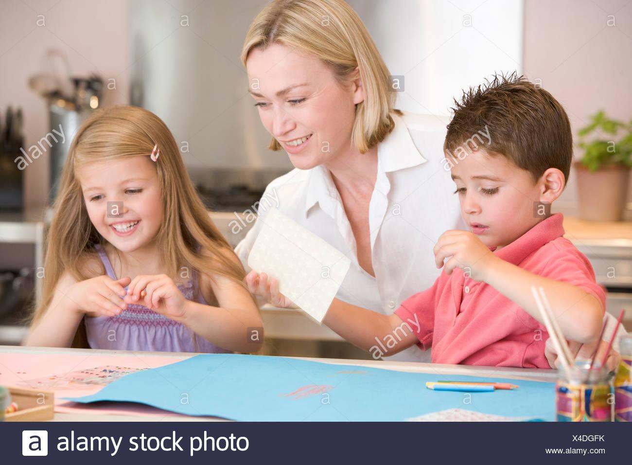 Una mujer y dos niños pequeños en la cocina con el proyecto de arte sonriendo Imagen De Stock
