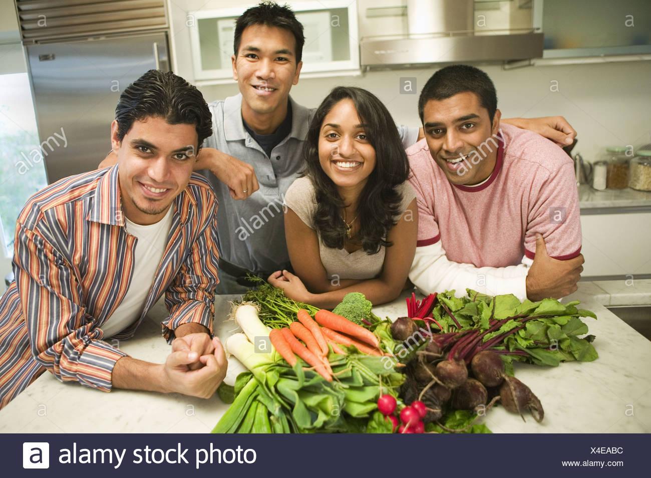 Grupo de jóvenes de etnias mixtas la celebración de verduras en la cocina Imagen De Stock
