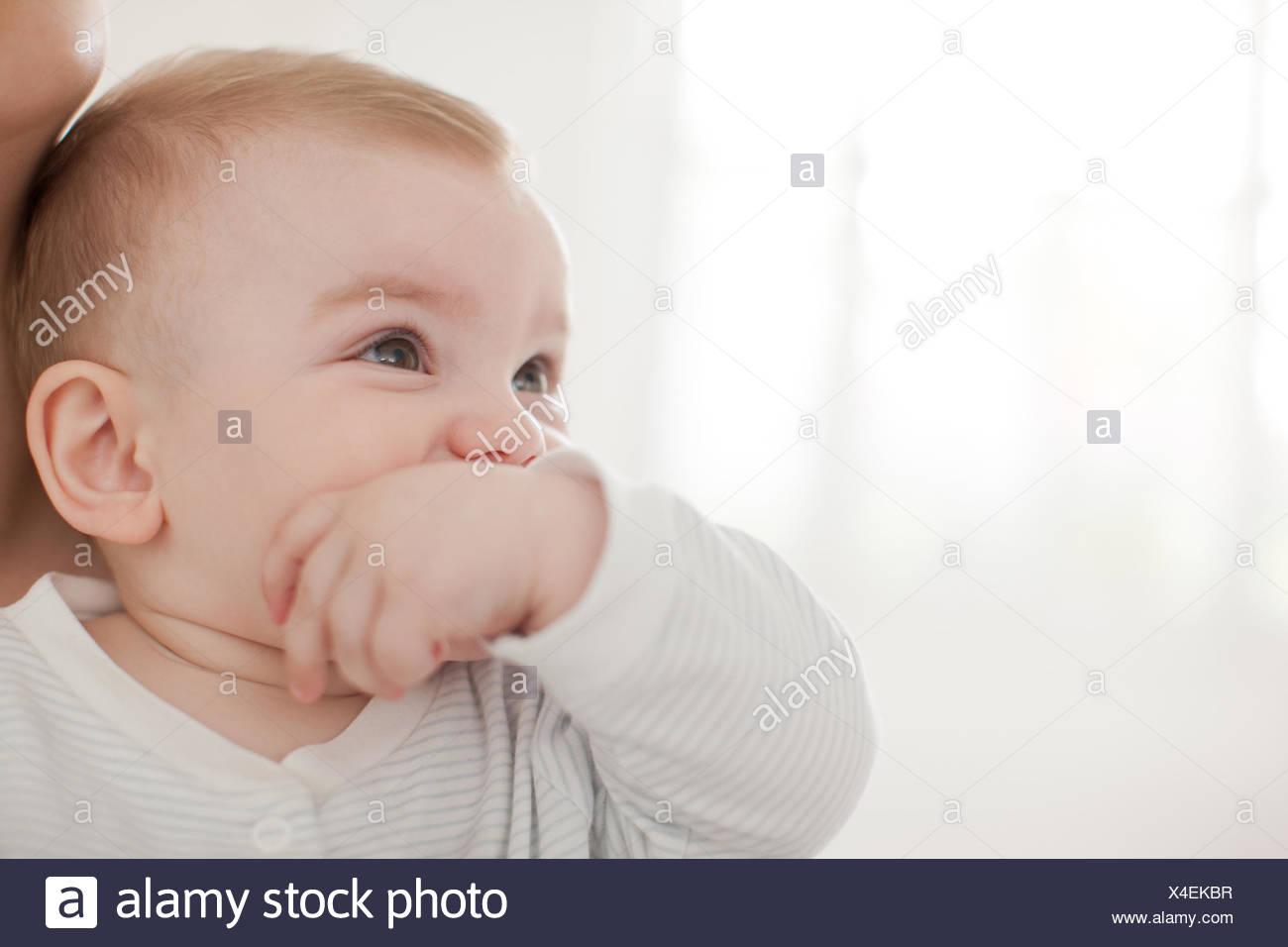 Bebé mordiendo el dedo pulgar en la boca Imagen De Stock