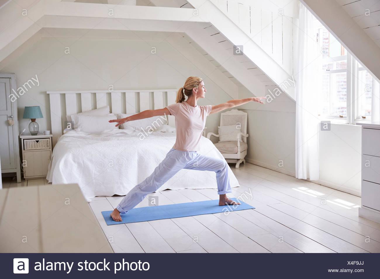 La mujer en el hogar comenzando mañana con ejercicios de yoga en la habitación Imagen De Stock