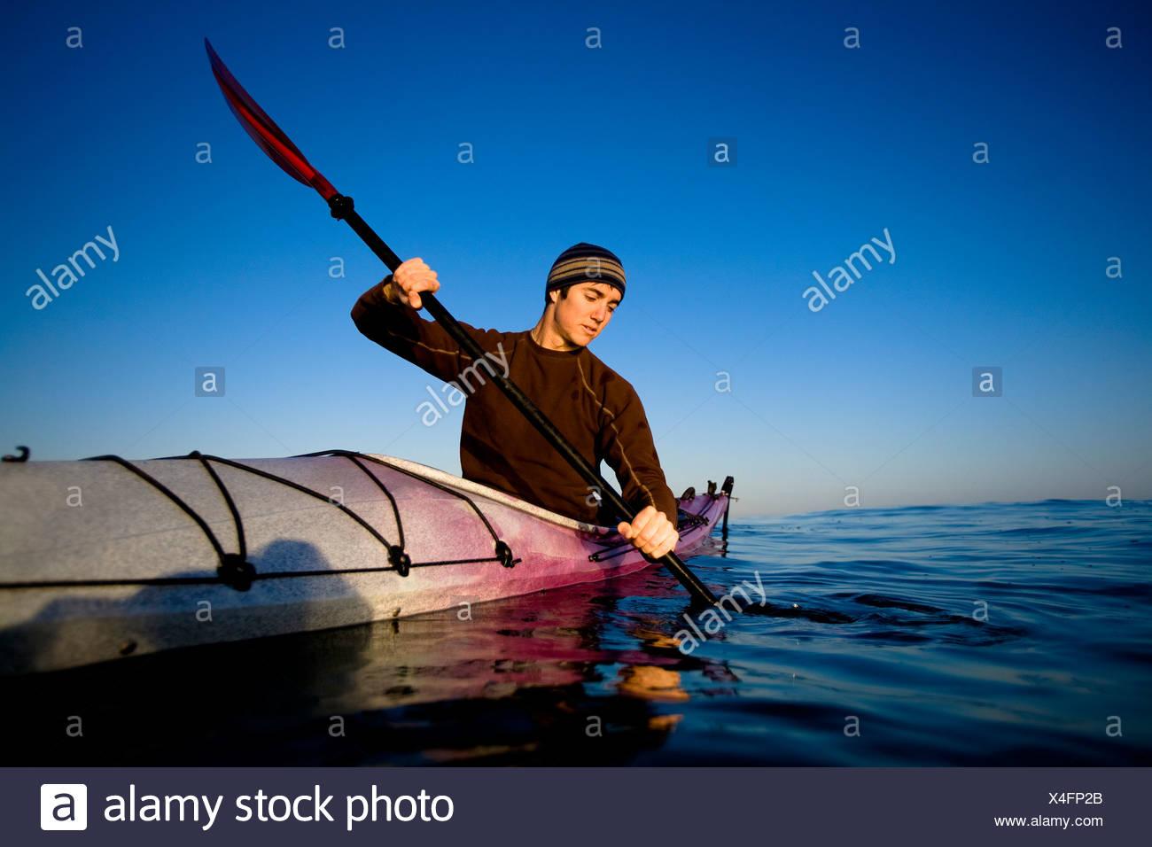 Un joven mira a su reflejo mientras remando un kayak de travesía, justo en las afueras de Ventura Harbor en Ventura. Imagen De Stock