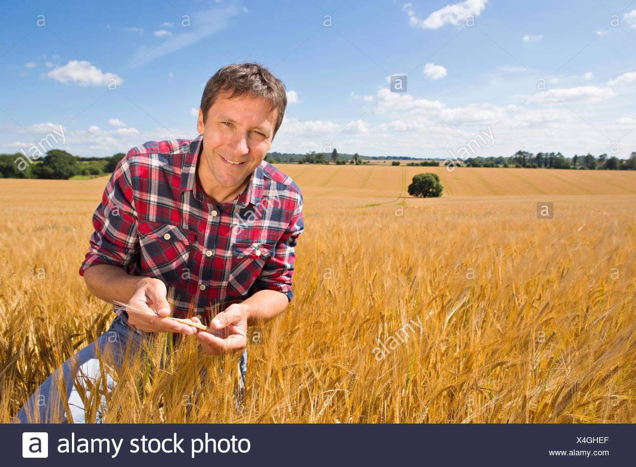 Retrato sonriente examinando agricultor rural soleado campo de cultivo de cebada en verano Imagen De Stock