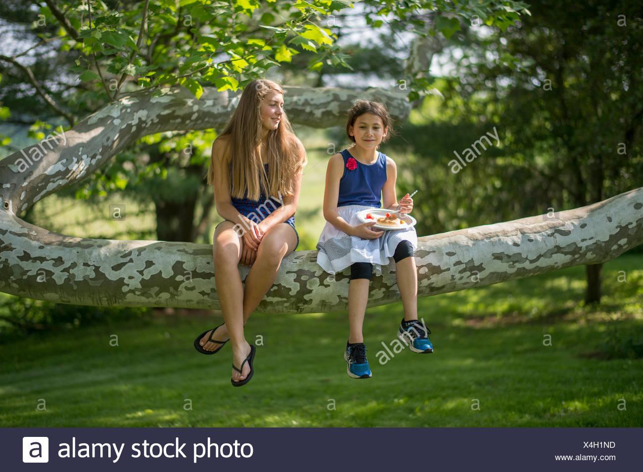 Dos niñas se sientan juntos en una gran rama del árbol. Imagen De Stock