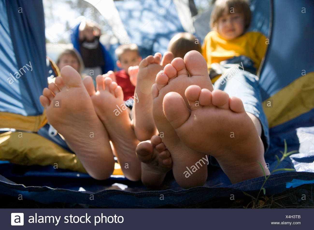 Vista de los pies de un niño asomando de una carpa Imagen De Stock
