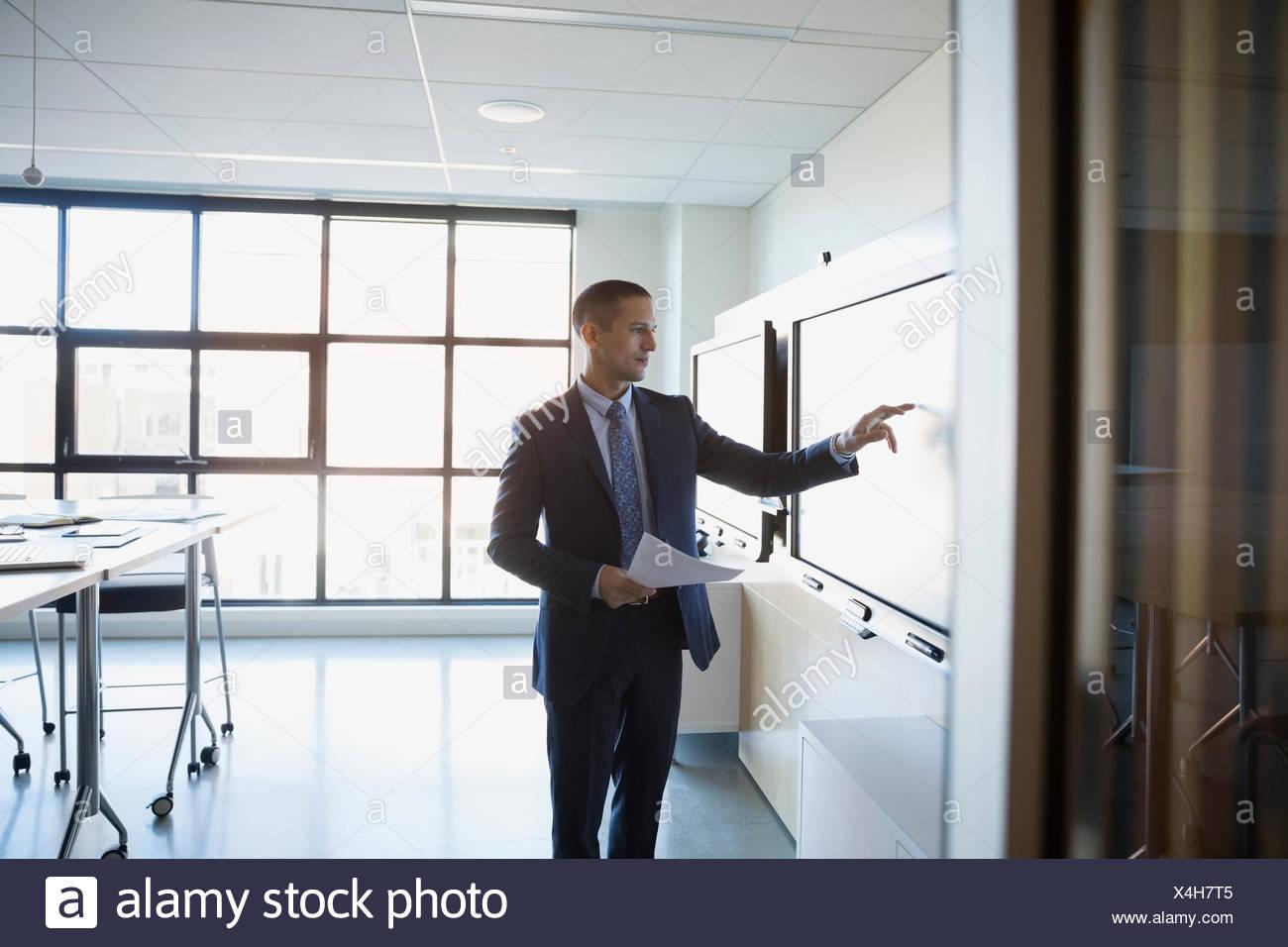 Empresario con la pantalla táctil en la sala Imagen De Stock