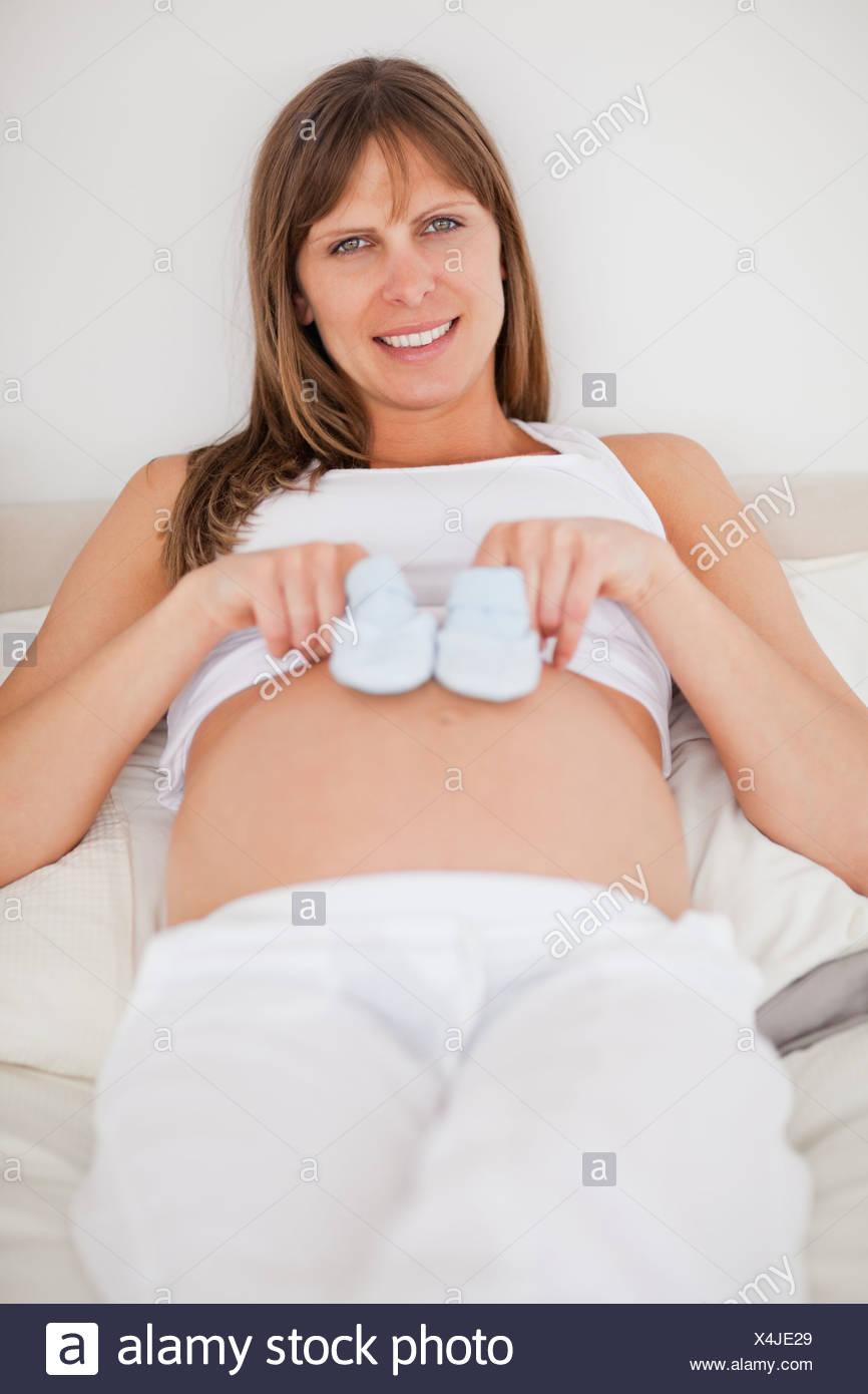 29173e2209 Hermosa mujer embarazada jugando con poco calcetines mientras está acostado  en una cama Imagen De Stock