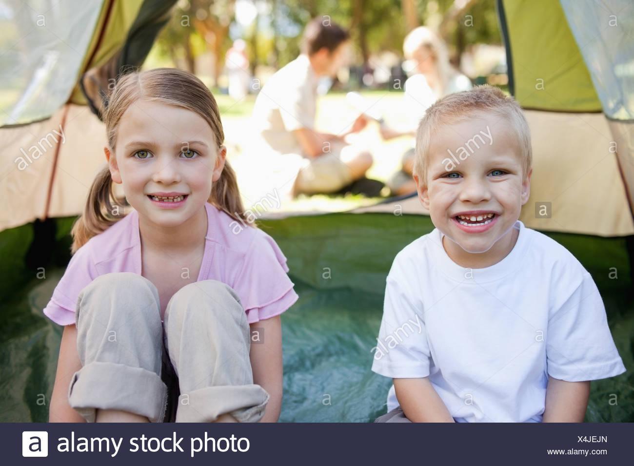 Una feliz pareja de chicos sentarse en el interior de la carpa mientras sus padres están fuera Foto de stock