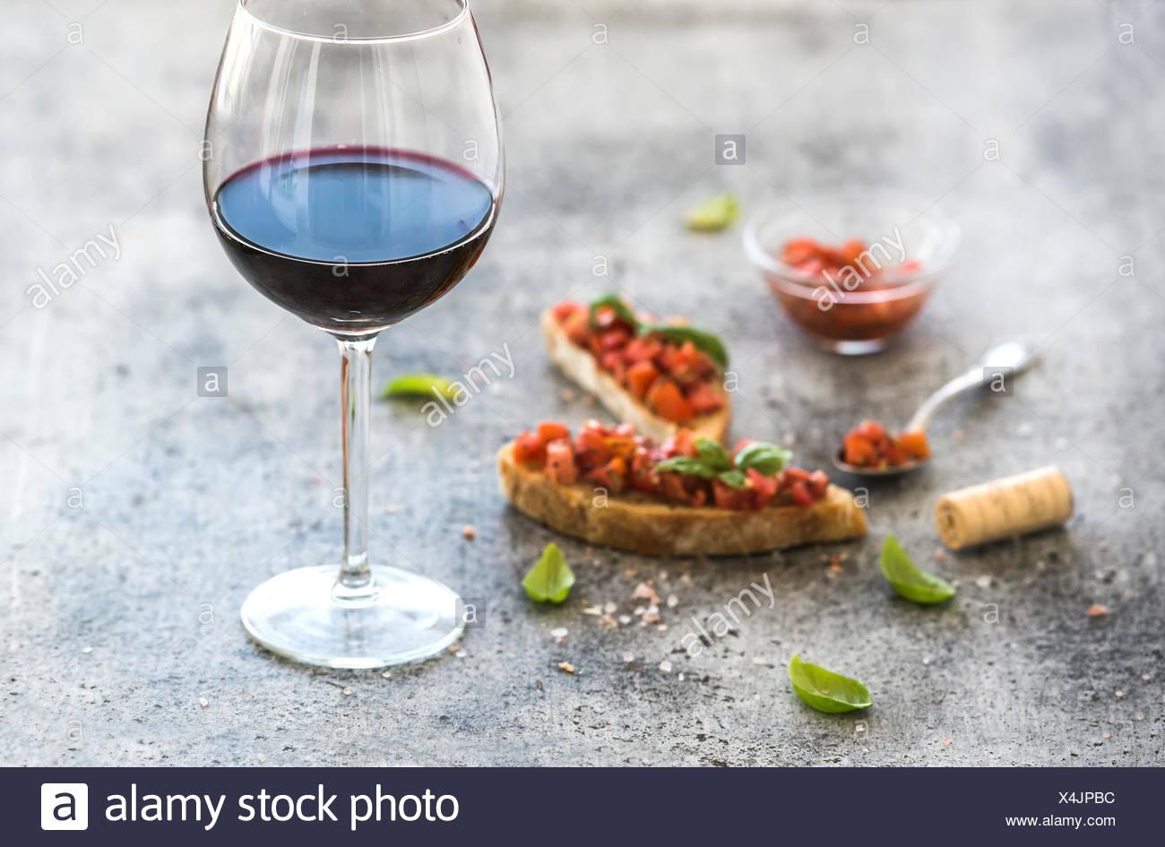 Copa de vino tinto y canapés con tomate y albahaca, el enfoque selectivo, composición horizontal Imagen De Stock