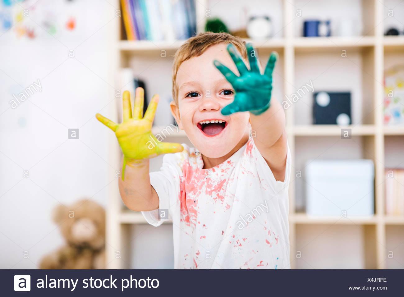 Retrato de niño sonriente mostrando sus manos pintadas Foto de stock