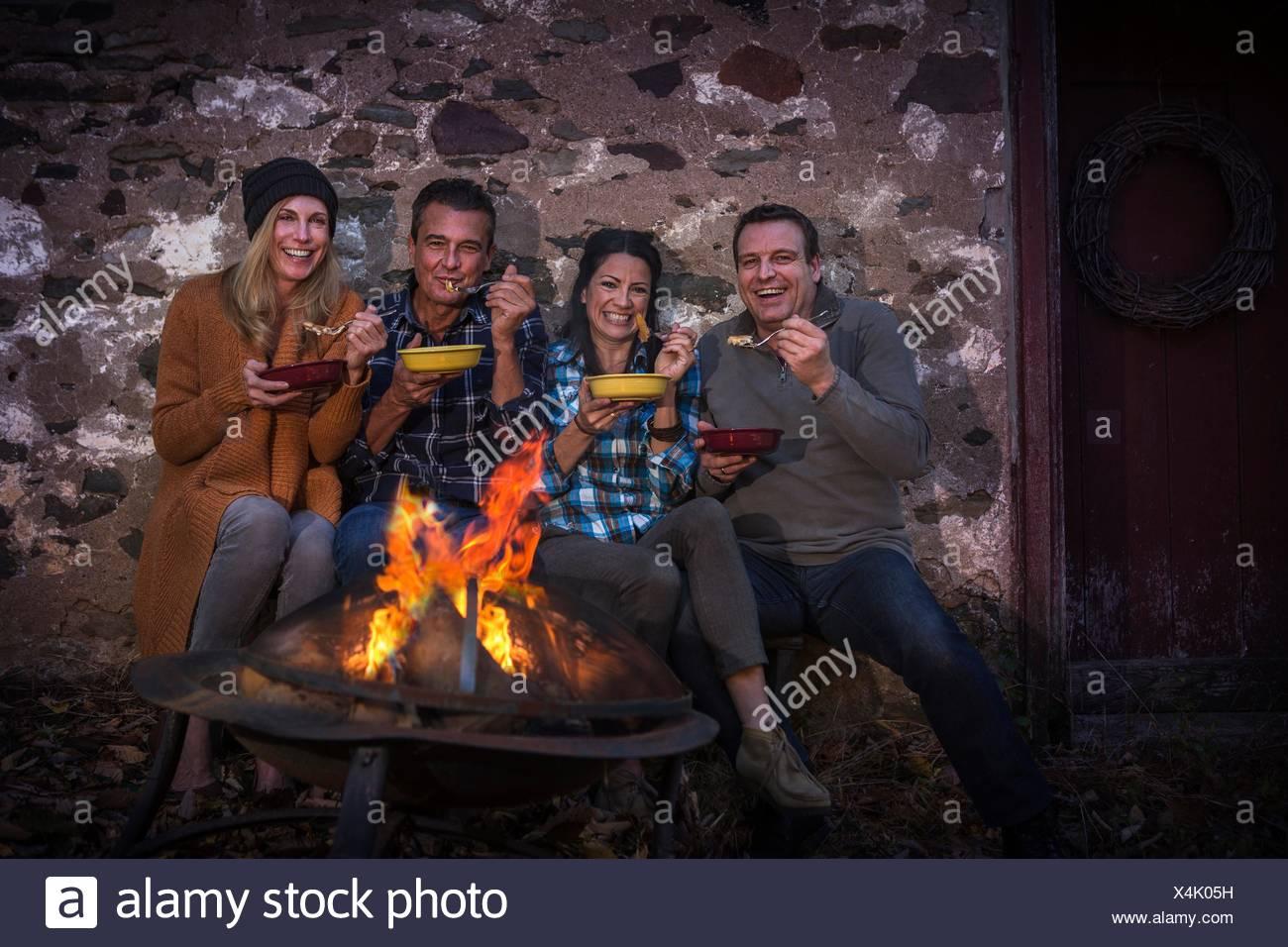 Retrato de dos parejas maduras comer delante de una fogata en la noche Foto de stock