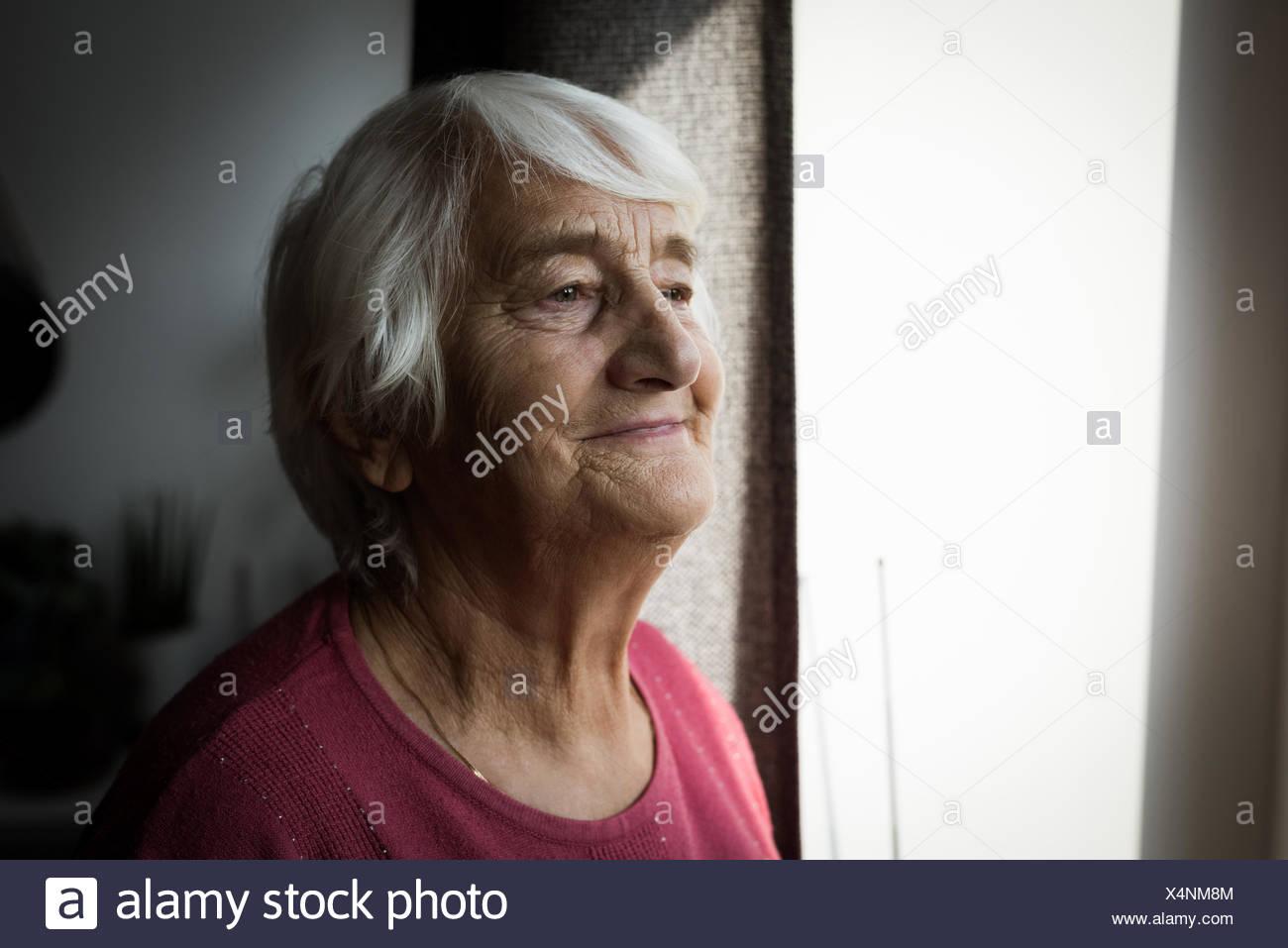 Mujer de pie cerca de la ventana superior Imagen De Stock