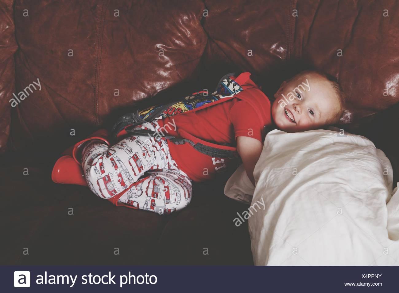 Muchacho tumbado en el sofá y sonriente Imagen De Stock