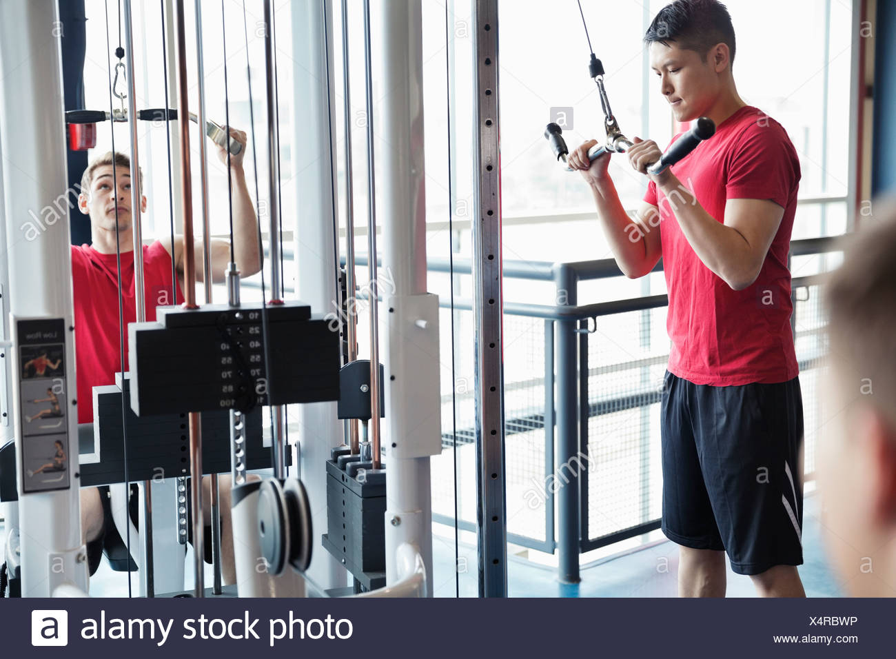 Los hombres usando máquinas de pesas en el gimnasio Imagen De Stock