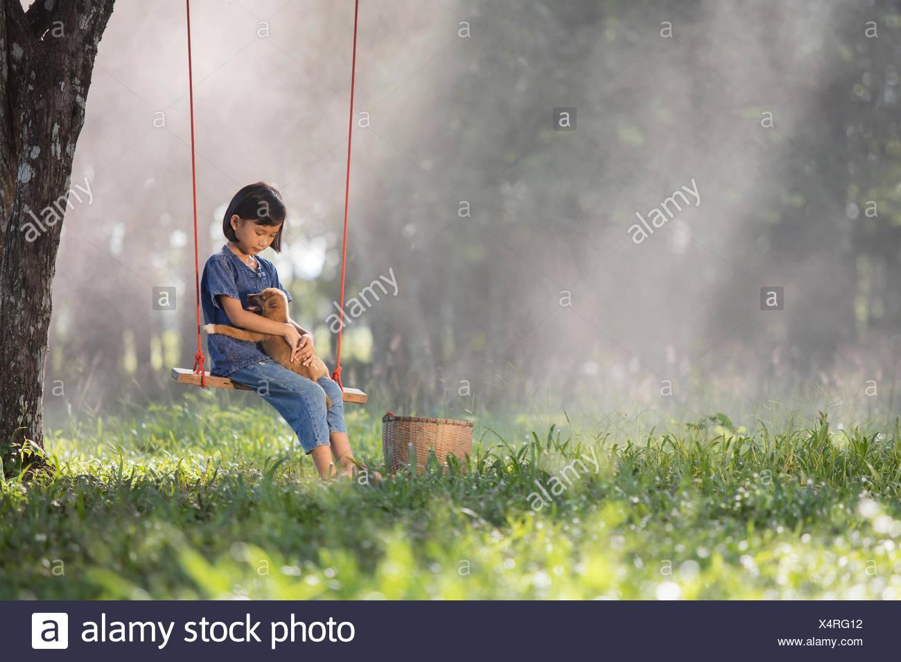 Chica sentada en un columpio con perro en su regazo Foto de stock