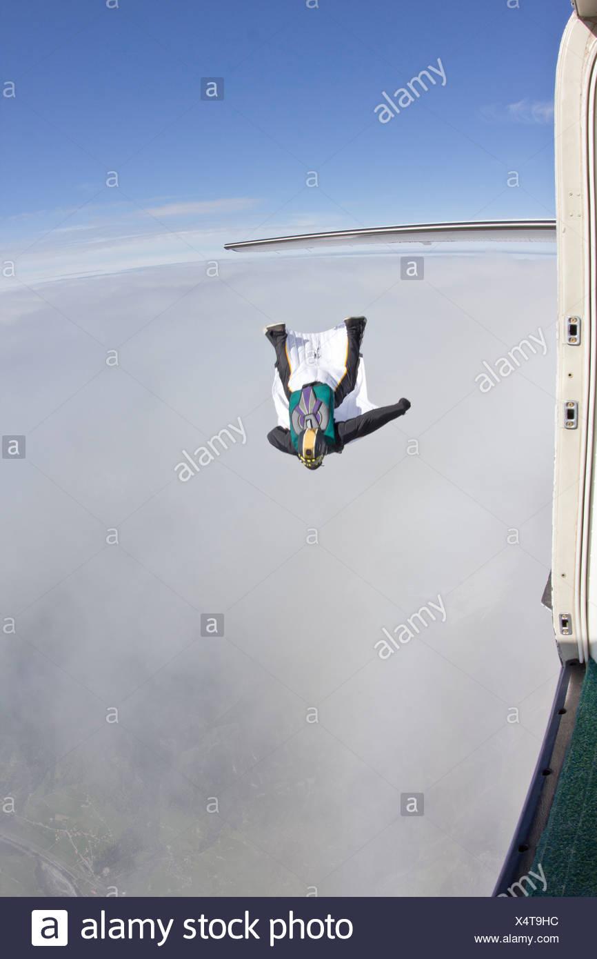 Mitad hombre adulto volando por encima de las nubes en wingsuit Imagen De Stock