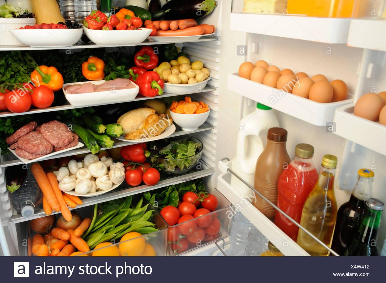 Vista interior de la nevera con estantes llenos de alimentos frescos Imagen De Stock