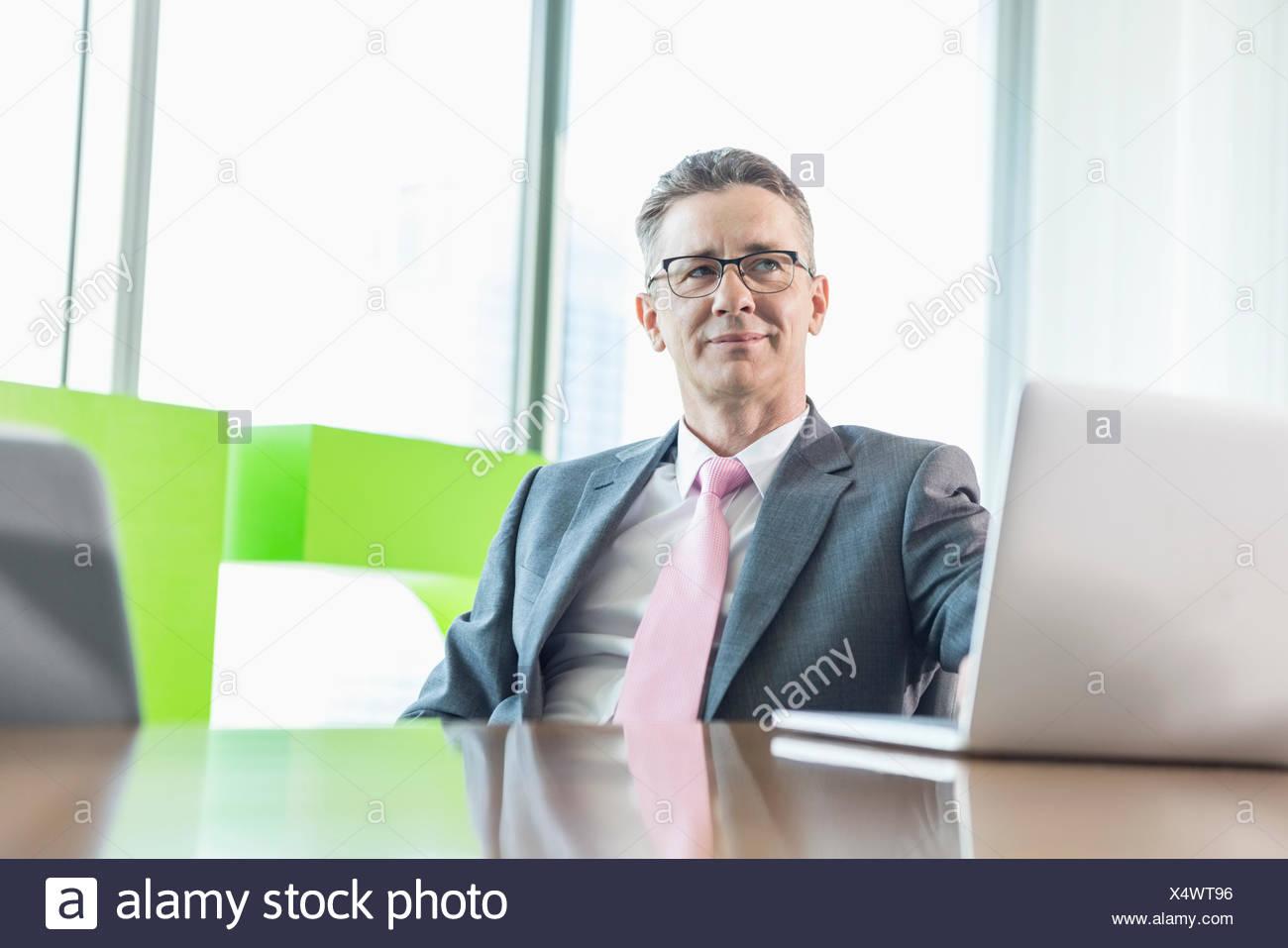 Empresario de mediana edad con laptop sentado en una mesa de conferencias Imagen De Stock