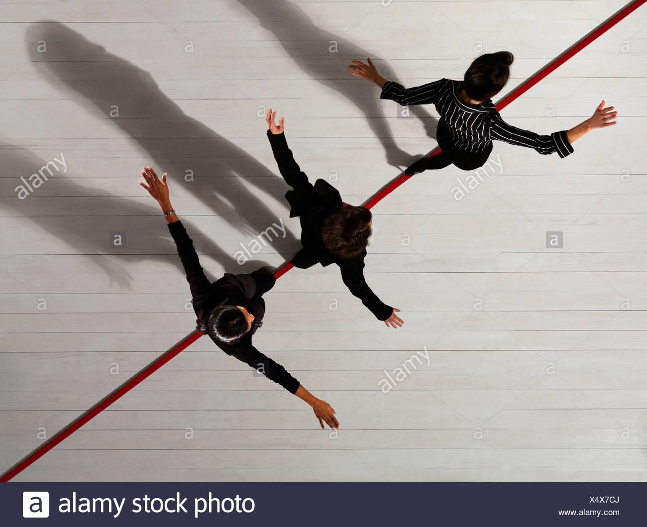 Las mujeres de negocios caminando a lo largo de línea roja Imagen De Stock