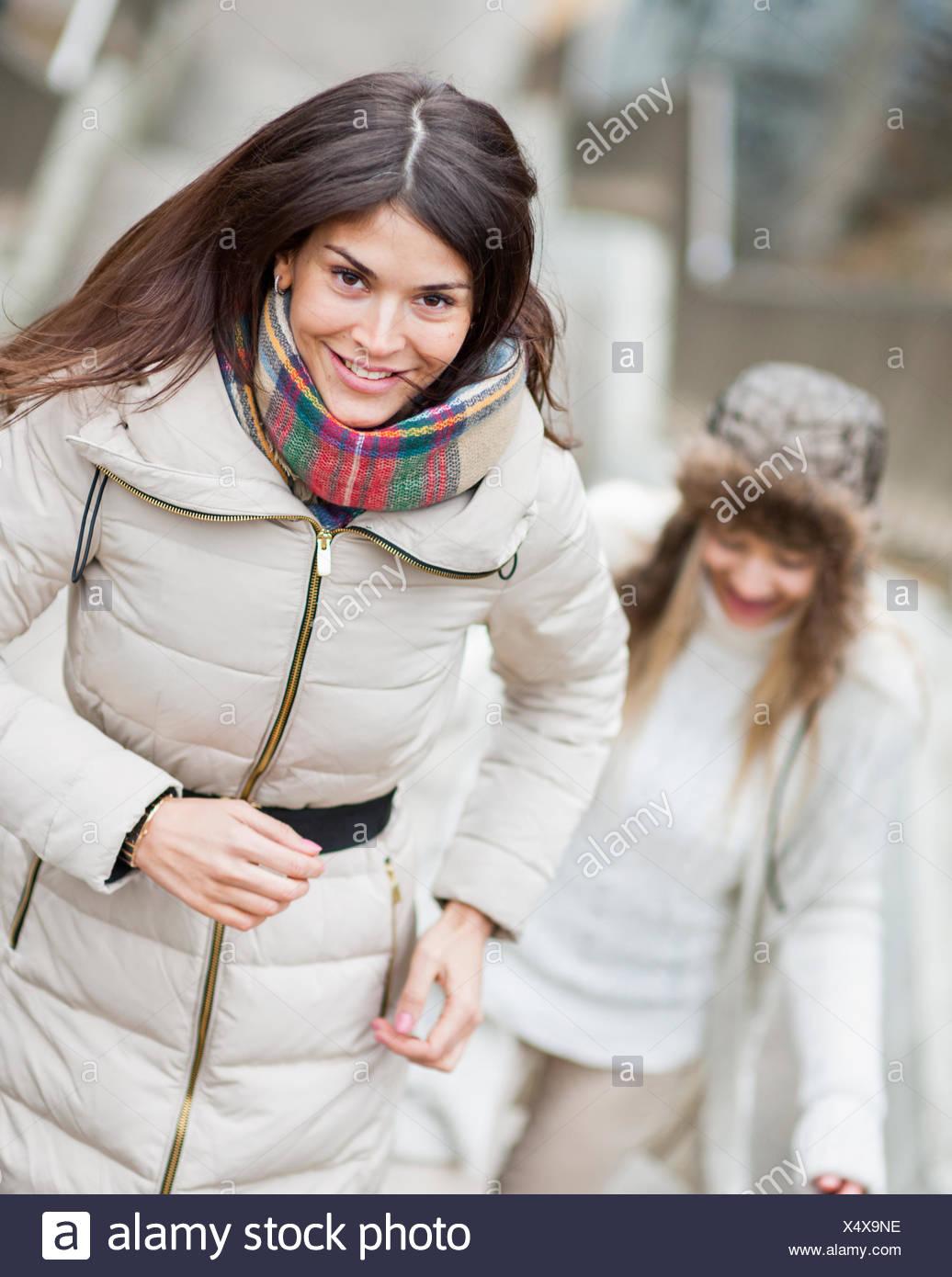 Mujer sonriente subir escaleras con un amigo en el exterior Imagen De Stock