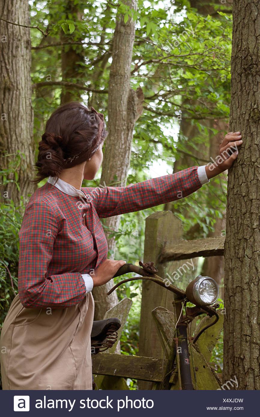 Joven en VINTAGE DRESS de pie con la vieja bicicleta en maderas Imagen De Stock