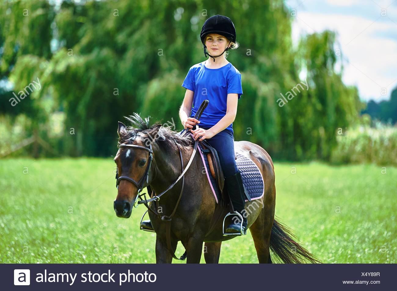 Vista frontal de la niña a caballo vistiendo un sombrero de montar, mirando a la cámara sonriendo Imagen De Stock