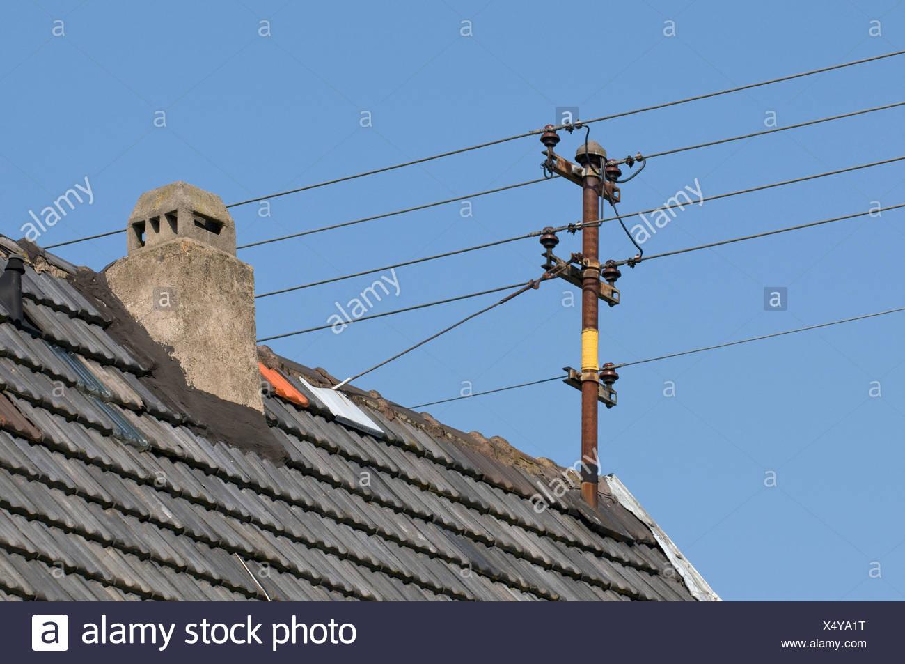 Antiguas líneas aéreas de energía doméstica con aislantes cerámicos en el techo Imagen De Stock
