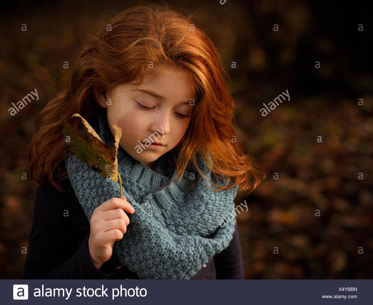 Pelo rojo Chica sujetando hoja de otoño Imagen De Stock