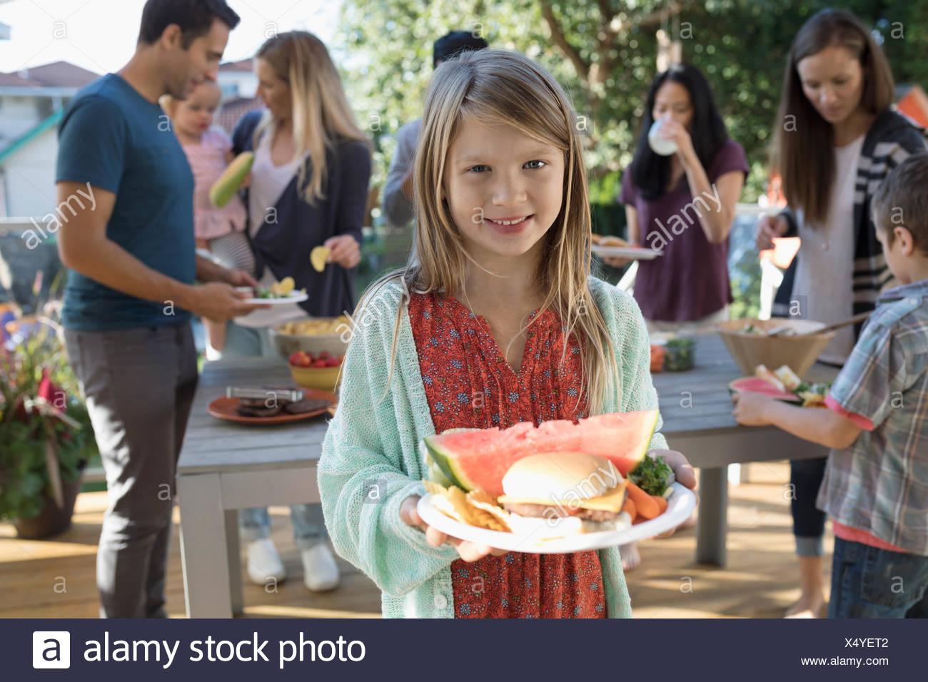 Retrato chica sonriente con la sandía y el Cheeseburger en barbacoa en el patio Imagen De Stock