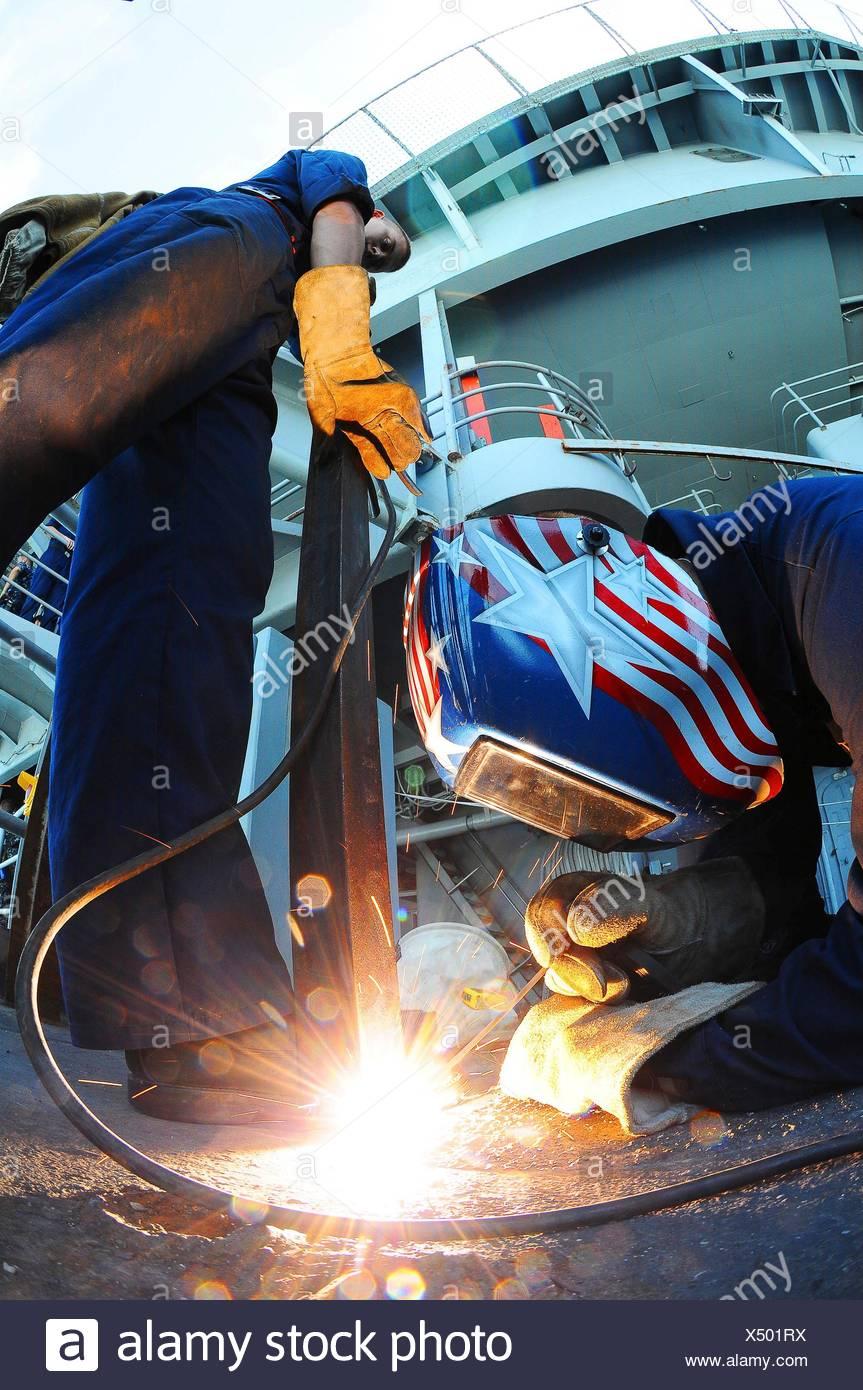 Océano Pacífico Septiembre 14, 2010 técnico de mantenimiento Casco Bombero Josh Hazelett soldaduras un bracketing de hierro para la cubierta mientras Hull Foto de stock