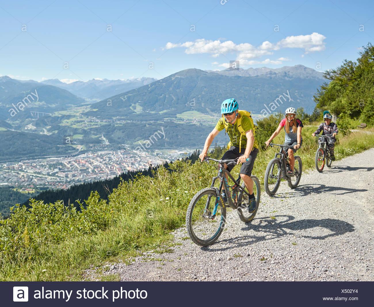 Familia en bicicletas de montaña, camino de tierra, Innsbruck detrás, Valle Inn, Tirol, Austria Imagen De Stock