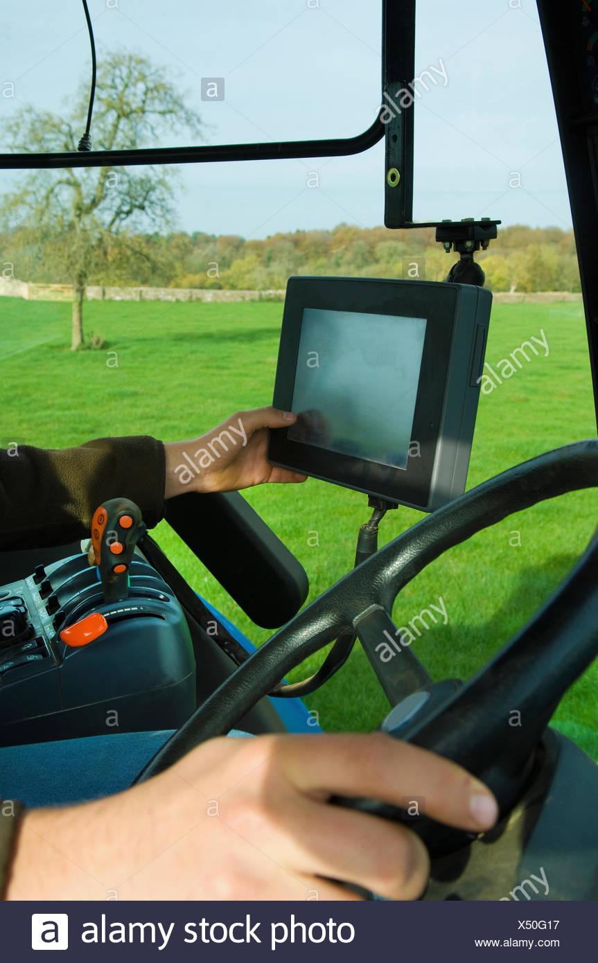 Los equipos técnicos a bordo de un tractor, una mano tocando una pantalla táctil. Imagen De Stock