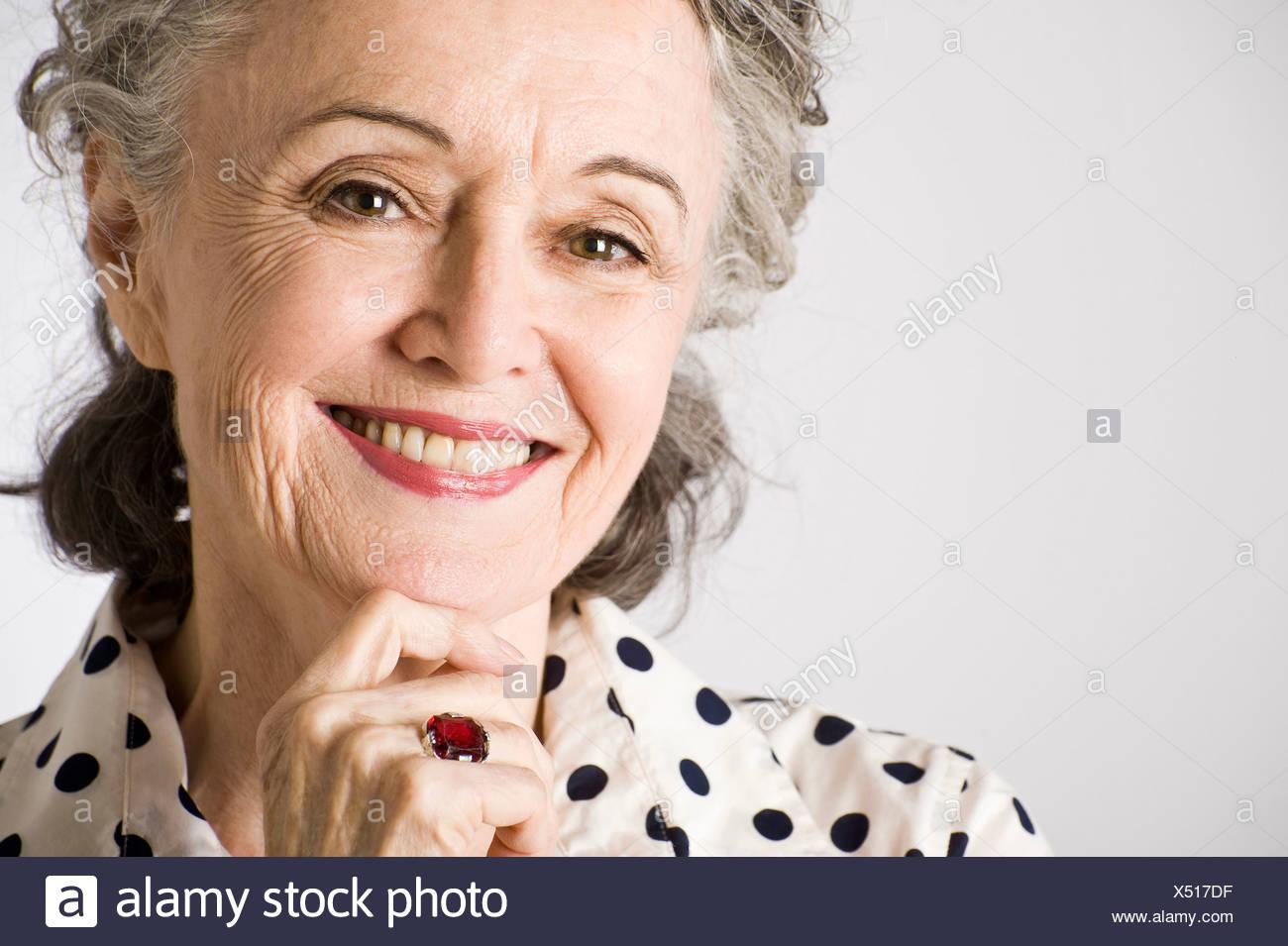 Retrato de mujer mayor, con la mano en el mentón, sonriendo Imagen De Stock