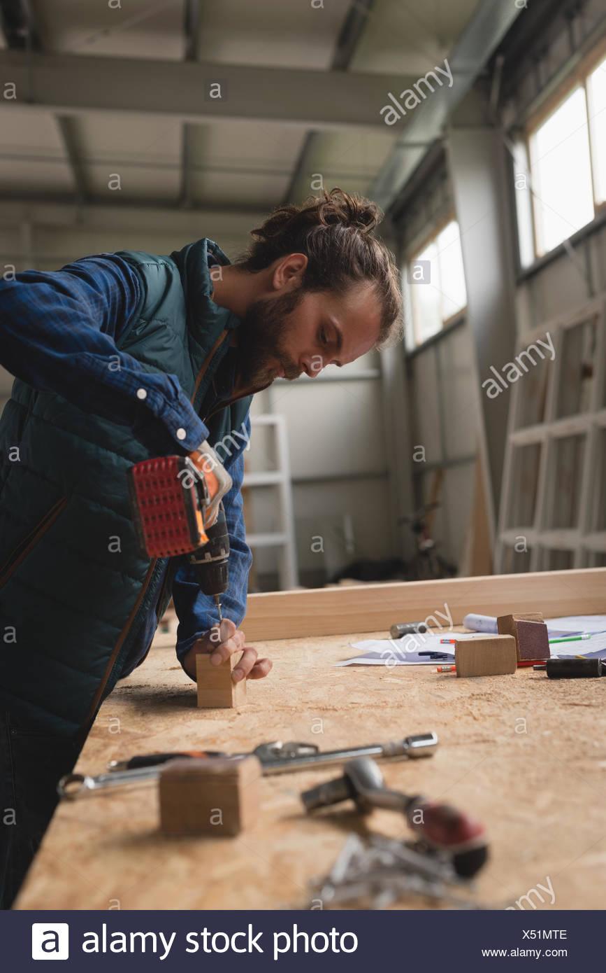 Carpenter haciendo el agujero en el bloque de madera con pistola de tornillo Imagen De Stock