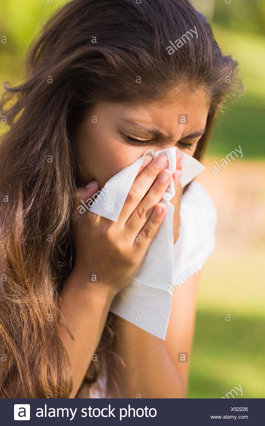 Mujer sonarse la nariz con un pañuelo de papel Imagen De Stock