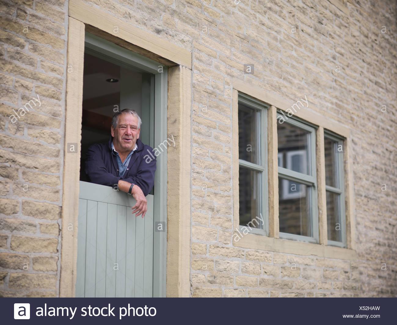 Retrato del agricultor madura mirando desde la puerta de granja Imagen De Stock
