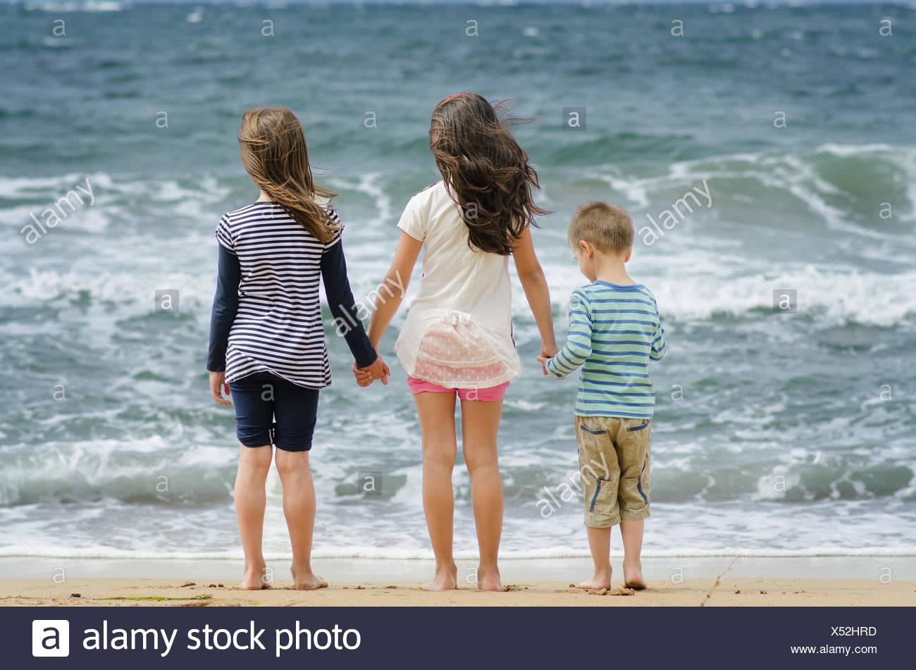 Bulgaria, dos niñas y un niño (8-9) (4-5) se sitúa en la línea de surf por manos mirando el mar Imagen De Stock