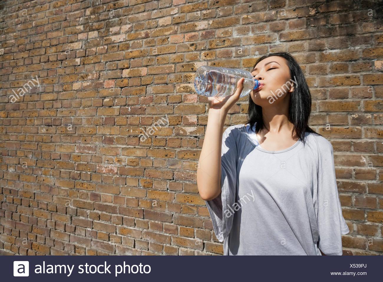 Hermosa joven agua potable contra la pared de ladrillo Imagen De Stock