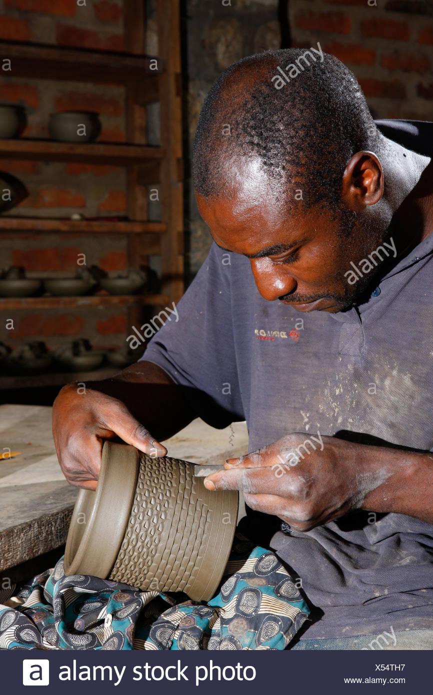 Hombre decorar una vasija de barro con adornos, la fabricación de cerámica, Bamessing, Camerún, África Imagen De Stock