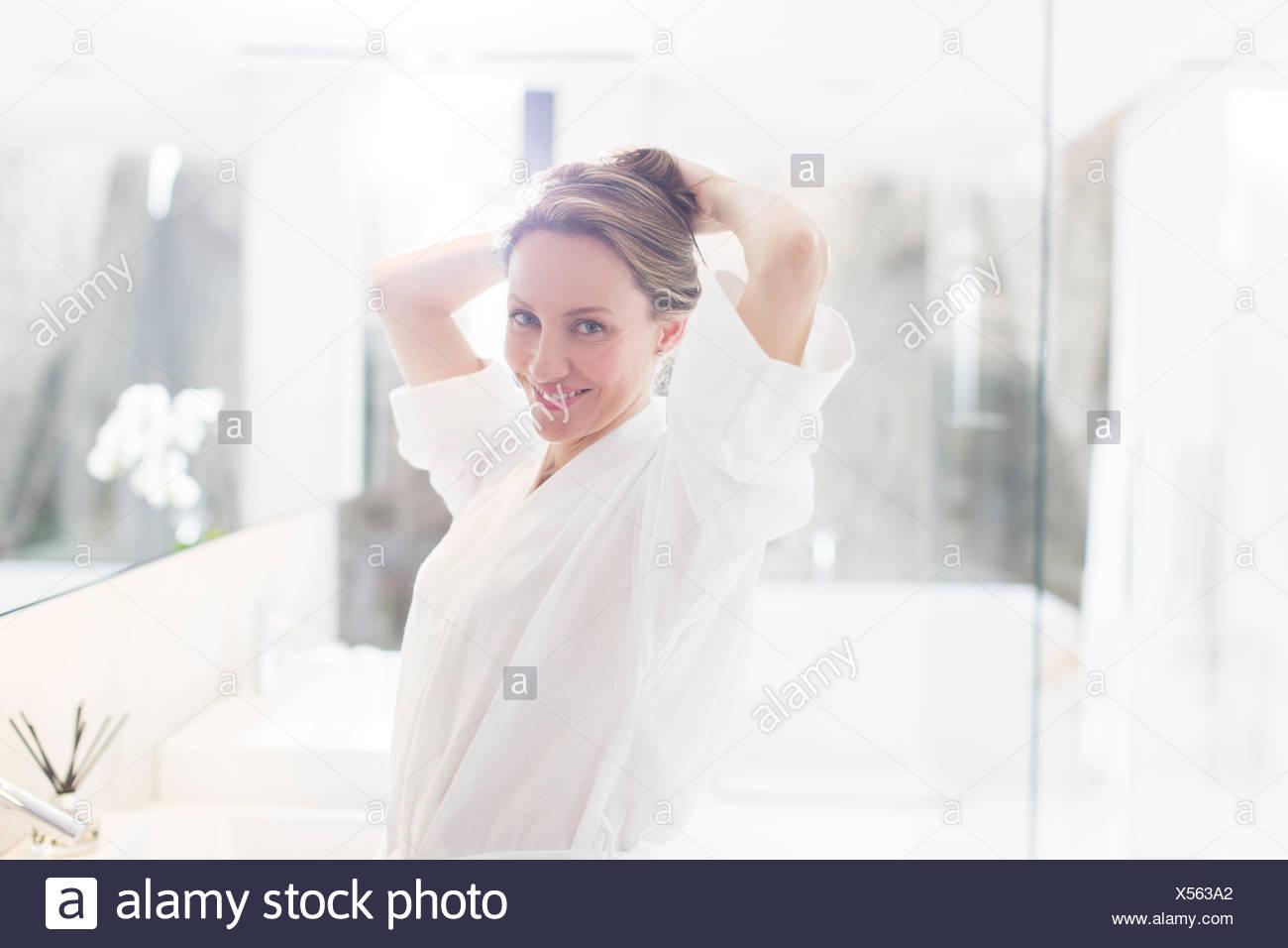 Mujer poniendo su cabello en el baño. Imagen De Stock