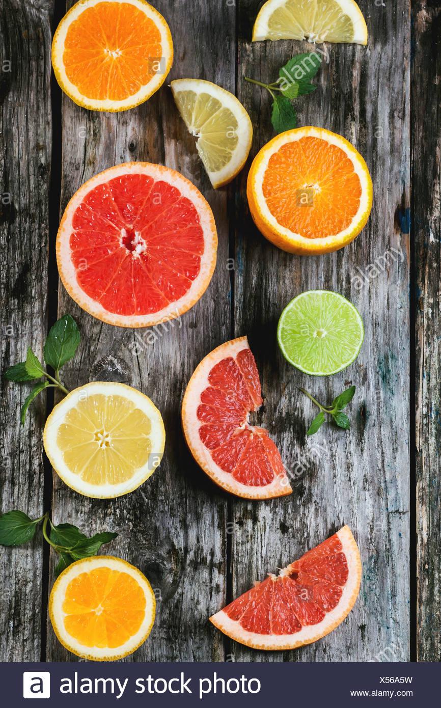 Conjunto de rodajas de cítricos limón, lima, naranja, pomelo con menta sobre fondo de madera. Vista desde arriba. Imagen De Stock