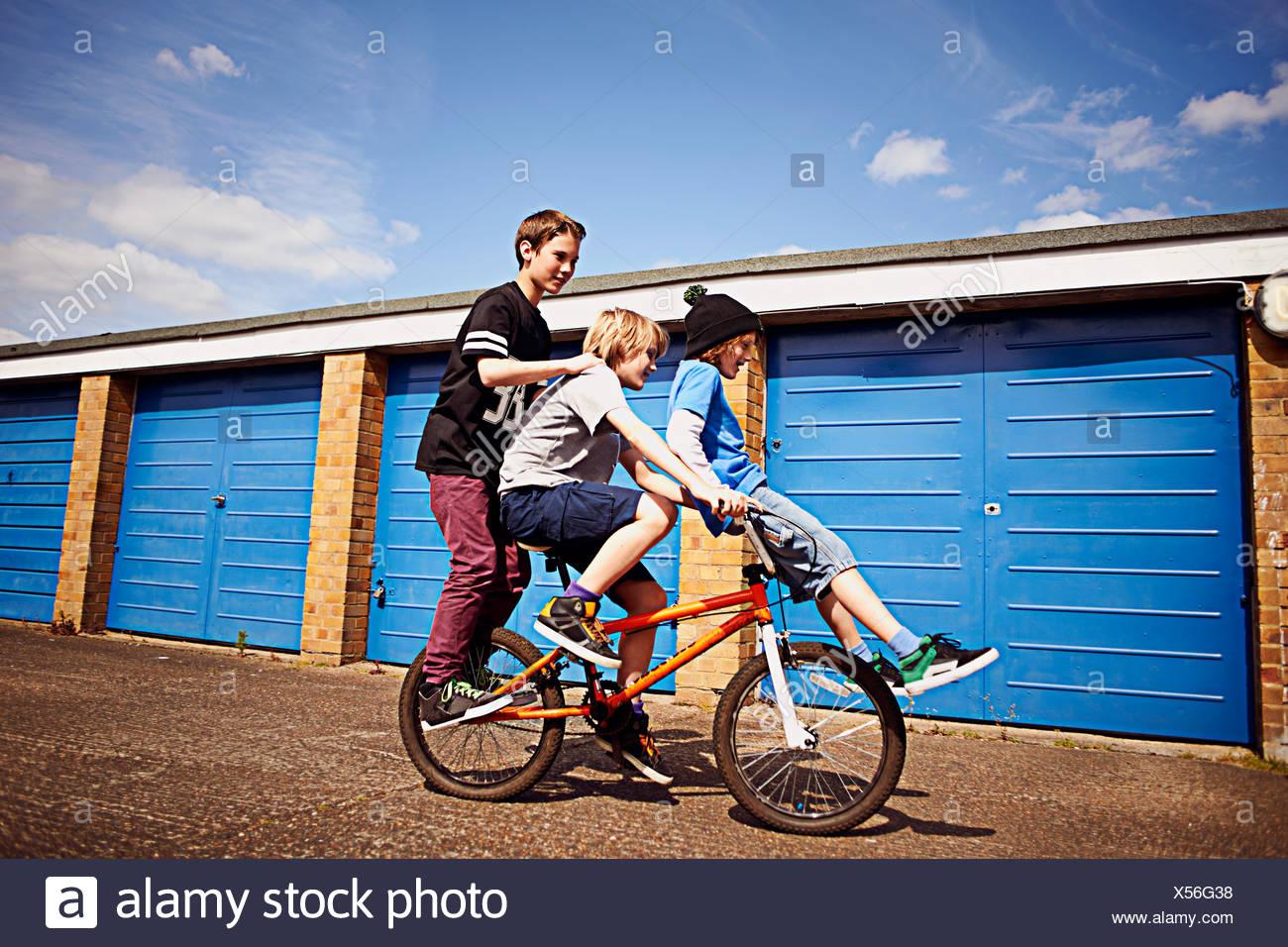 Boy dando dos amigos de un paseo en bicicleta Foto de stock